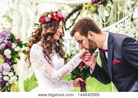 groom kisses hand of bride on wedding ceremony. wedding arch.