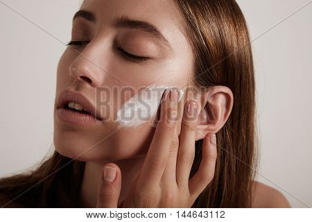 Woman Put Cream On A Cheek. Ideal Young Skin Concept