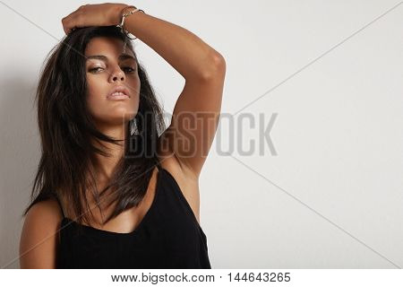 Spanish Brunette Woman Touching Hair And Watching At Camera
