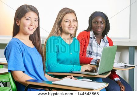 Interracial group of girls working in team at their high school