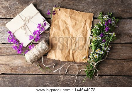 Crumpled paper, thread, envelope and bunch of delphinium and chamomile flowers on wooden background, top view