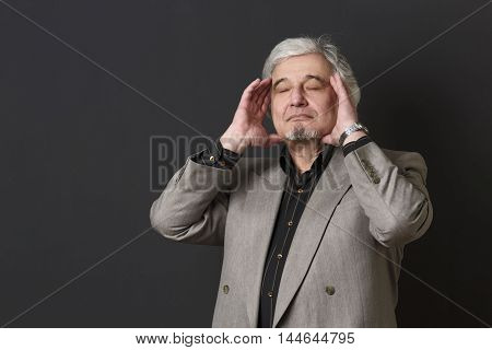 Portrait of professor man touching his face isolated on black background. Teacher man of university or colleage in studio.