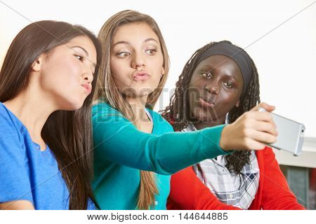 Three teenage girls taking a selfie and making silly faces at school