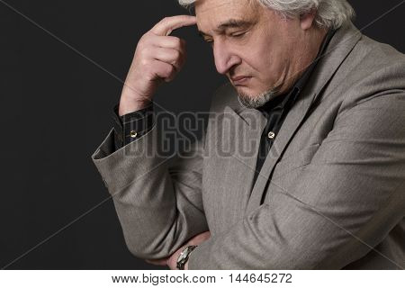 Portrait of professor man of university or colleage thinking about theories and concepts in studio. Teacher man posing with closed eyes over black background.