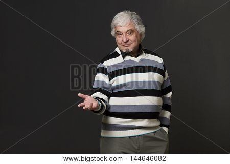 Portrait of handsome professor man of university or colleage showing his arm while explaining new theory, concept, prove in studio.