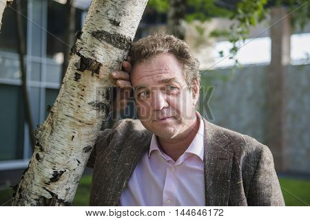 Russian businessman standing at the birch