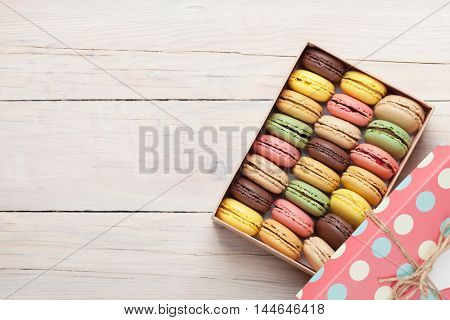 Colorful macaroons in a gift box on wooden table. Sweet macarons. Top view with copy space