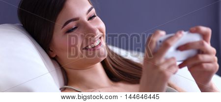 Cheerful pretty woman in her living room lying on the couch sending messages
