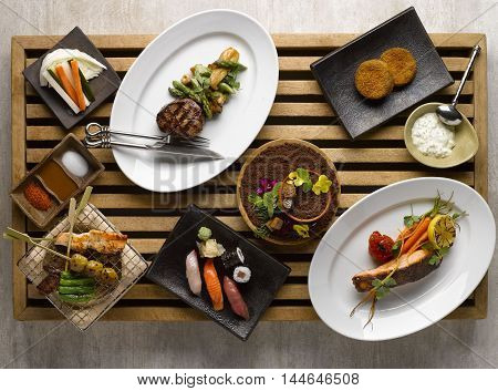 Japanese dinner set mezza with sushi roasted beef snapper vegetables on wooden tray