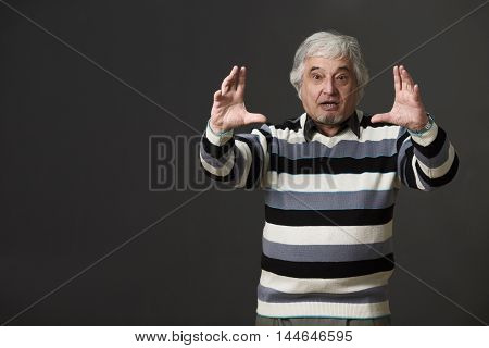 Professor man of university or colleage giving two hands while explaining new material to students or pupils isolated on black background in studio.