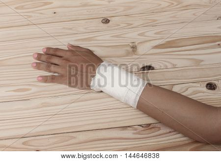 Gauze bandage the hand contusion. treating patients with hand  a wrist left male with wrapping his injury on wood table.