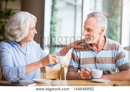 Warm atmosphere. Positive delighted senior couple sitting at the table and drinking coffee while having a nice conversation