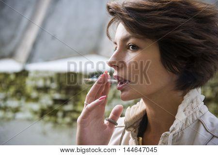 Young woman smokes on the street, selective focus