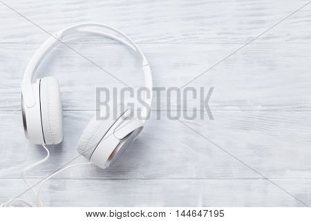 White headphones for music sound on wooden table. Top view with copy space for your text