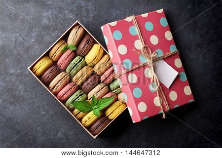 Colorful macaroons in a gift box on stone table. Sweet macarons. Top view
