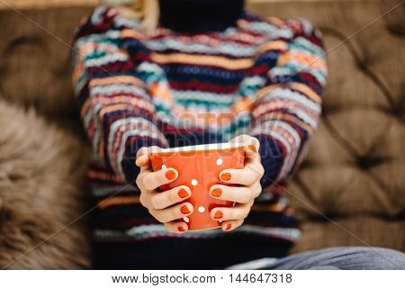 Female hands with hot drink, home background