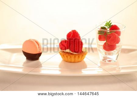 Cream and cake with redberry in glass on white plate