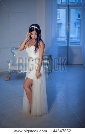 Young attractive girl in tiara and white dress