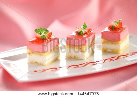 Pudding cake with mint leaves and strawberry on white plate with tea