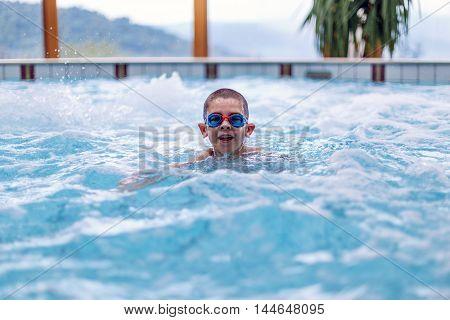 Happy kid in swimming pool, indoor shot