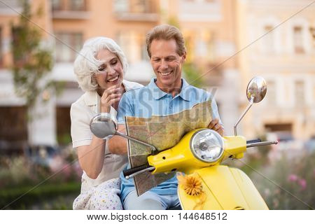 Couple on scooter is smiling. Mature man holding a map. This map is upside down. Jokes on the way home.