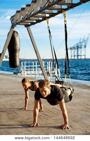 Young beautiful sportive people training with trx near sea.