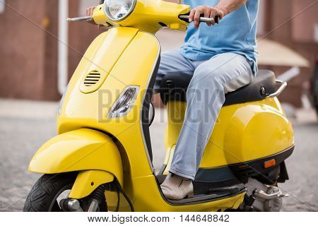 Man sitting on a scooter. Scooter of yellow color. Ride with comfort. New and shiny.