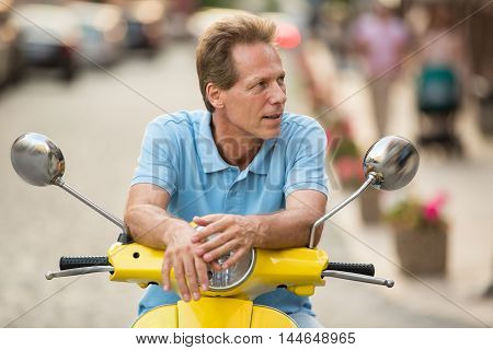 Mature man sitting on scooter. Guy looks to the side. The road will be long. Vacation spent in the city.