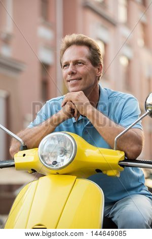 Mature guy with smiling face. Man is sitting on scooter. Tourist in town. Next destination is waiting.