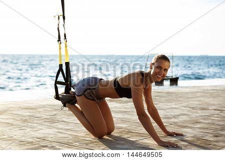 Young beautiful sportive girl training with trx near sea.