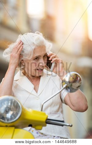 Lady with phone on scooter. Mature woman touches hair. Small talk on the way. I will meet you soon.