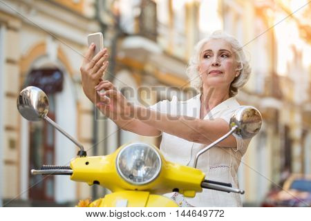Adult woman looks at phone. Lady on a scooter. Make some calls during trip. Long list of numbers.