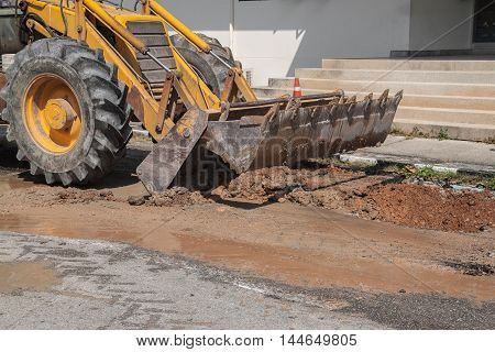 Excavator working on the Repair of pipe water and sewerage on road Worker using  to dig a hole to fix