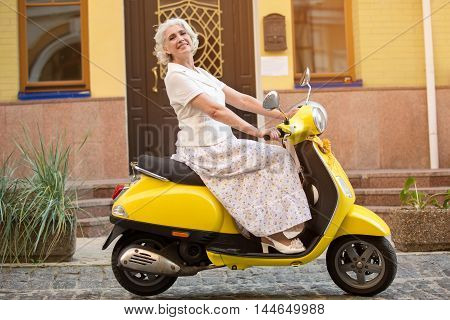 Mature lady rides a scooter. Side view of yellow scooter. Traveller rides with comfort. Trip won't take much time.