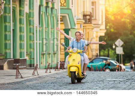 Couple rides yellow scooter. Mature woman with raised arms. Trip brings fun. Just ride along the road.