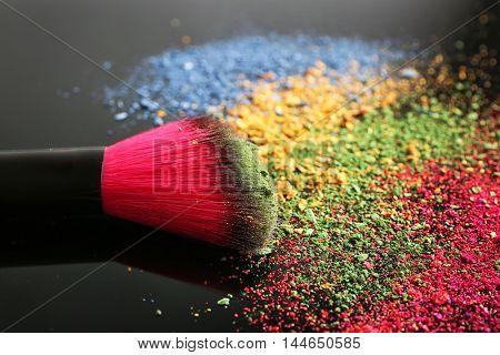 Make up brush and colourful eye shadows on black background