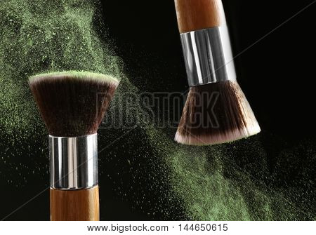 Make-up brush with green powder explosion on black background