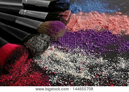 Make up brushes and colourful eye shadows on black background