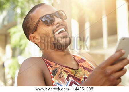 Human Emotions And Feelings. Cute Charismatic Dark-skinned Man Holding Smart Phone, Laughing Out Lou