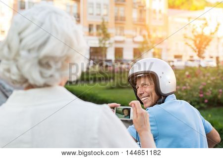 Adult man in helmet smiling. Lady is holding a camera. I'll make some photos. Remember these moments.