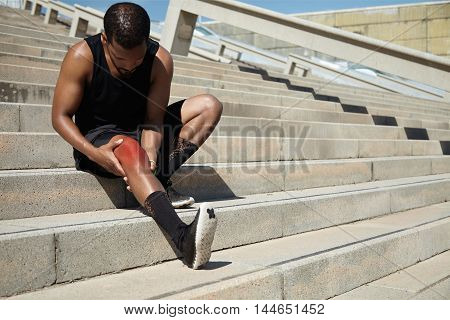 Attractive Dark-skinned Male Runner Wearing Black Outfit Sitting On Stairs Outdoors, Massaging His A