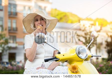 Woman is eating ice cream. Mature lady on a scooter. Delicious dessert for a tourist. Spend time in fresh air.