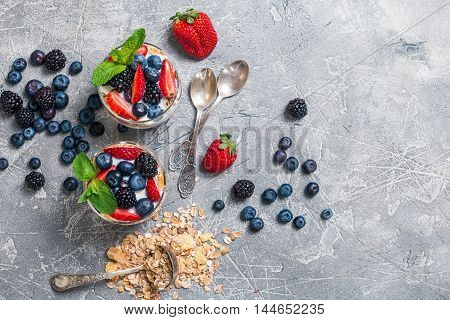 Baked granola with  yogurt and berries in glasses, on gray background, top view.
