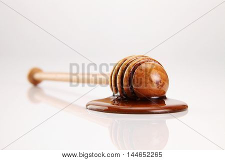 wooden honey dipper with honey on white background