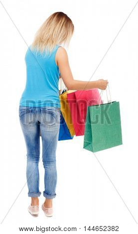 back view of woman with shopping bags. backside view of person. Isolated over white background. The blonde in a blue shirt and jeans looks into colored packets.