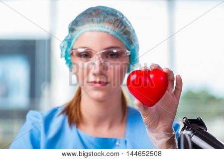 Doctor holding red heart in medical concept