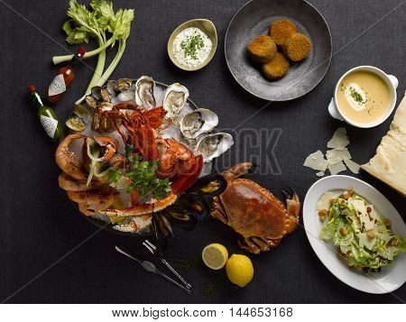 The deli mezza seafood meal with crab lobsters shrimp oyster clams mussel lemon lettuce and soup on the table
