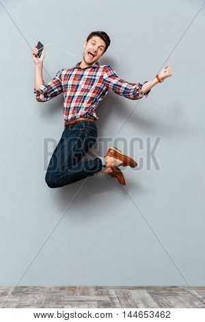 Happy excited young man listening to music from cell phone and jumping over grey background