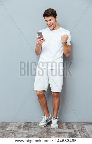 Happy attractive young man with earphones and smartphone celebrating success over gray background