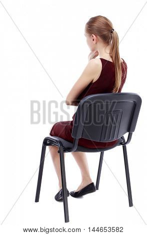 back view of young beautiful woman sitting on chair. girl watching. Isolated over white background. A girl in a burgundy dress sitting on a chair listening intently.
